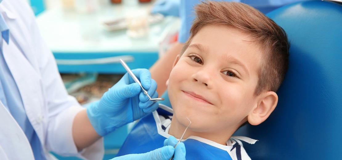 на фото ребенок в стоматологическом кабинете лечит зубы