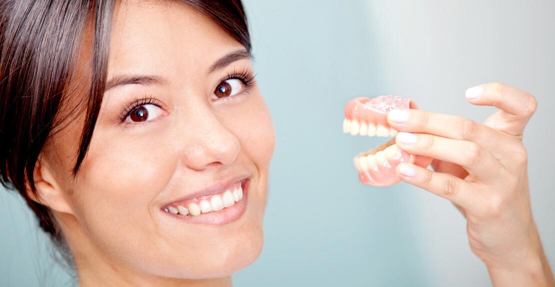 пациентка с макетом челюсти для подготовки к протезированию зубов у стоматолога хирурга