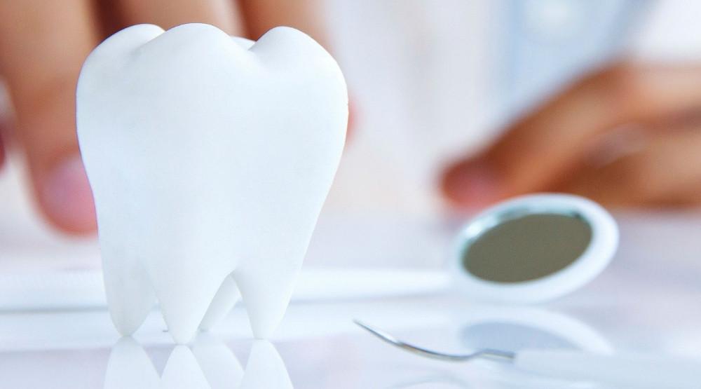 на фото макет зуба и стоматологический инструмент для лечения зубов под общим наркозом