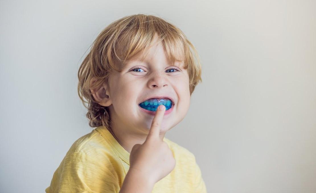 на фото ребенок с ортодонтической пластиной для исправления прикуса