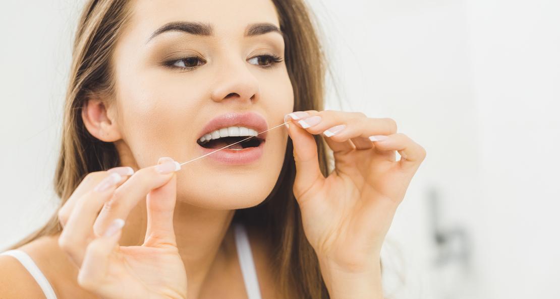 на фото девушка проводит гигиену полости рта с помощью зубной нити