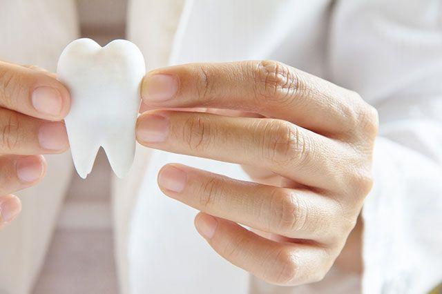 фото искусственного зуба в руках стоматолога